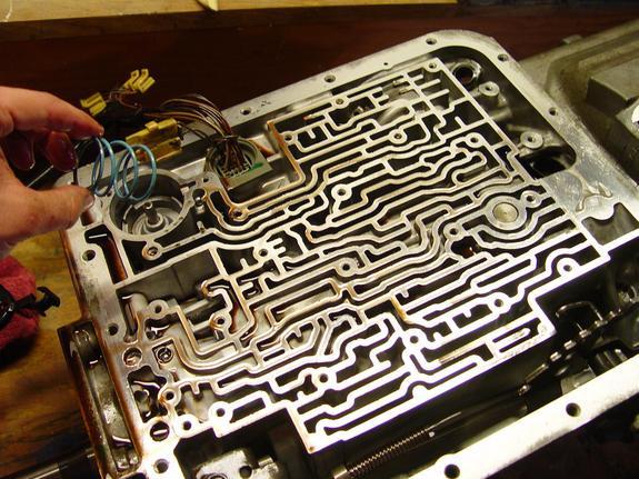 "4L60E波箱"" /> 3、拆下油底壳之后,见到滑阀箱总成 当预备拆卸低档及倒档超越离合器时,我看到这样的景遇: 4、拔出线束,拆下所有线圈。拆下变扭器锁止电磁阀线圈后才能拆出液力变矩器离合器电磁阀线圈。 [[img STYLE=""DispLAY: block; MArGin: 0px auto 10px; TexT-ALiGn: center"" ALT="""" src=""http://simg."