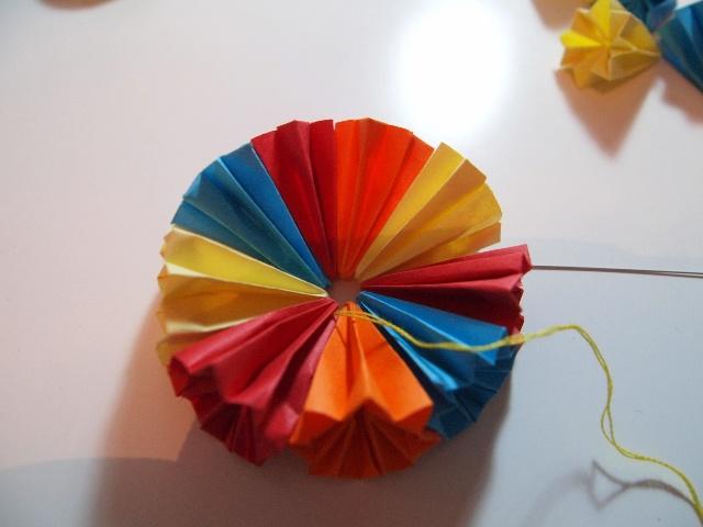 最近旺旺疯狂的迷上了折纸,主要是因为在幼儿园上课时老师教了一次折纸,折的啄木鸟,他在家当小老师,教我,说话的口吻和老师一样一样的,特别好玩,旺旺折他的,我自己折我自己的,想起很久以前学的一个花球。    挺好玩,也简单,就是比较耗时,如果一天趁有空折几个,凑到一定数目还是很有趣的,可以挂在孩子房间当个小装饰。      前面的九步都非常简单,最麻烦的就是全部拆开后要反过来按着折痕再来定型。   反过来之后按着压痕一个角一个角折。