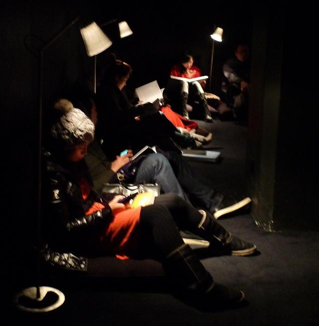 参观展览的人席地而坐,在台灯下认真看书是从未见过的场景.